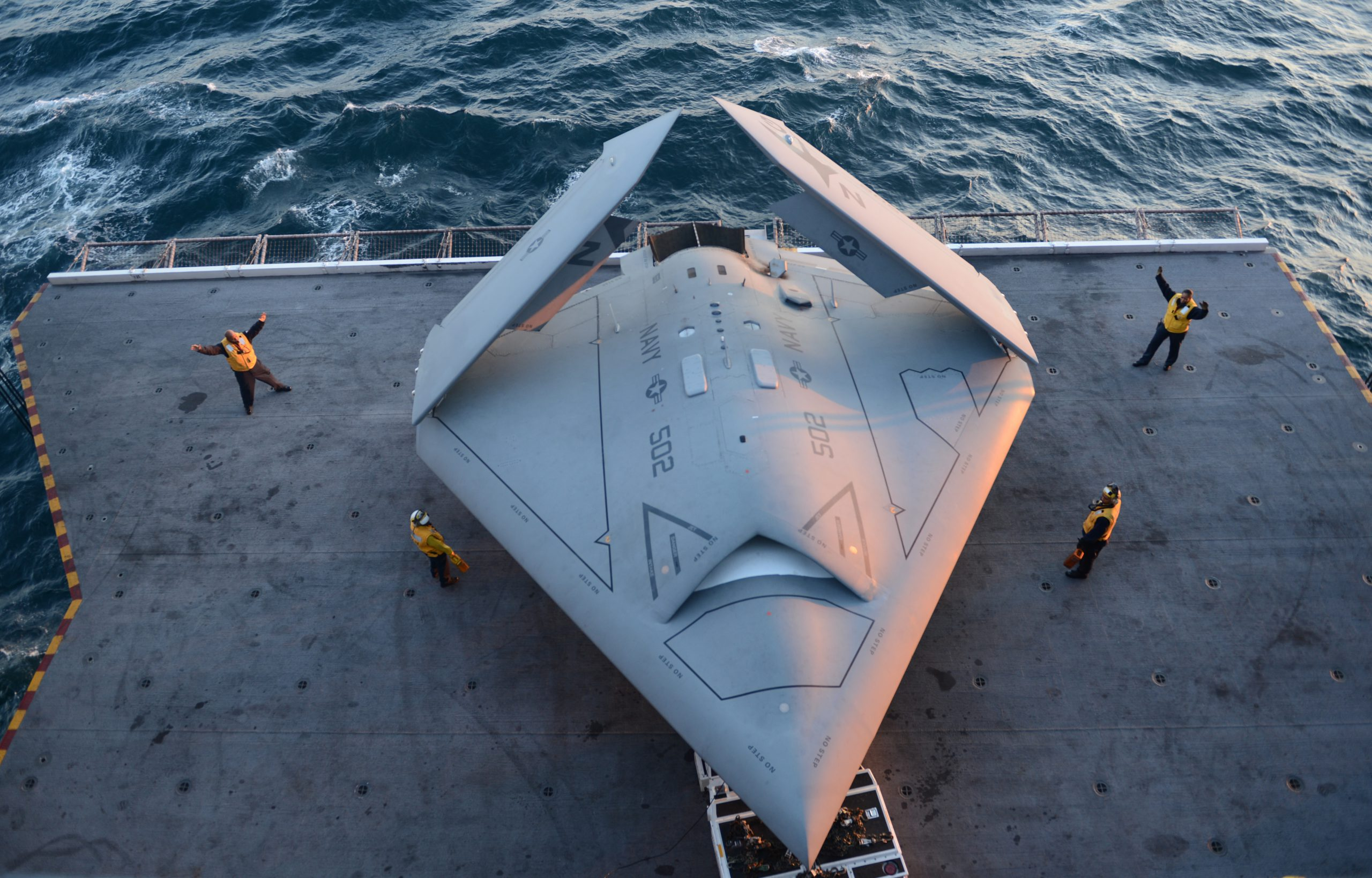 https://upload.wikimedia.org/wikipedia/commons/c/cd/U.S._Sailors_move_a_U.S._Navy_X-47B_Unmanned_Combat_Air_System_demonstrator_aircraft_onto_an_aircraft_elevator_aboard_the_aircraft_carrier_USS_George_H.W._Bush_%28CVN_77%29_May_14%2C_2013%2C_in_the_Atlantic_Ocean_130514-N-FU443-025.jpg